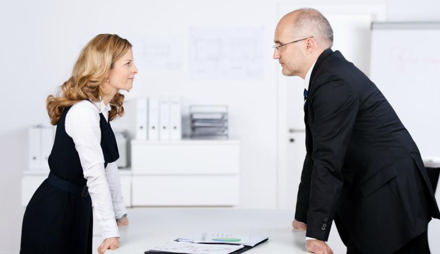 Chef und Mitarbeiterin stehen sich gegenüber