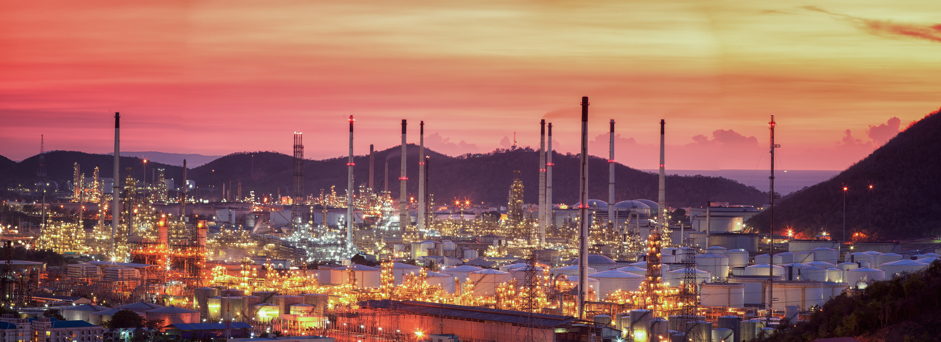 Oil refinery with tube and oil tank along twilight sky