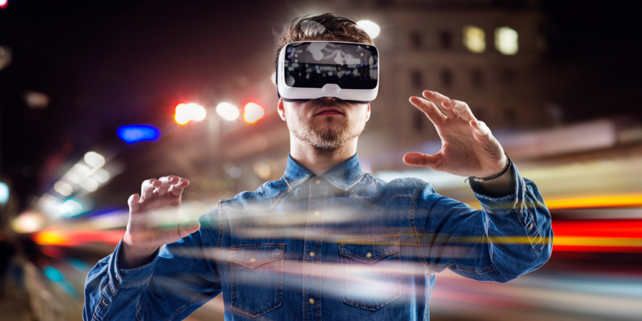 Double exposure of man wearing virtual reality goggles and night city